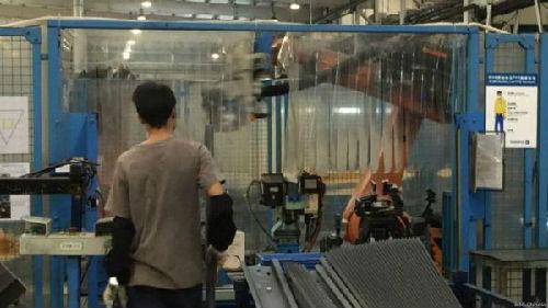 在东莞的海斯坦普汽车组件公司生产线上,工人和机器人合作完成汽车配件的生产。
