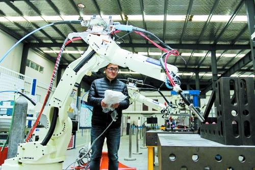 技术人员向记者演示工业机器人是如何进行工作的