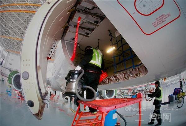 图为工作人员对飞机前货仓进行清洁