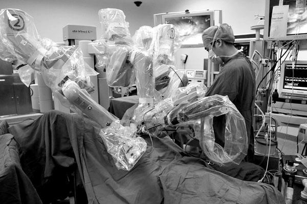 """安徽医科大学第一附属医院手术室内,泌尿外科专家操纵""""达芬奇""""手术机器人正在手术。"""