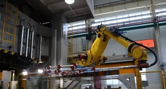 如图所示,在东风风行现代化生产基地,车门、车窗、车盖等车身零部件的冲压过程由巨大的机床完成,每道工序之间的搬运环节则由机器人完成。橘黄色机械手臂的手掌是真空吸附器,可以轻松吸附起巨大、不规则的车身部件,送到下一个冲压设备。冲压工序完成后,质检机器人开始工作,通过摄像头、激光等技术检测成品是否有瑕疵。在冲压车间现场,仅需少量工人负责监控或调整设备。高度自动化的冲压生产线,将尺寸误差降到最低,带来较高的良品率,并大幅提高生产节拍。人工冲压汽车侧围件,一分钟只能冲压三四件,机器人能冲压六七件,而且不良率最