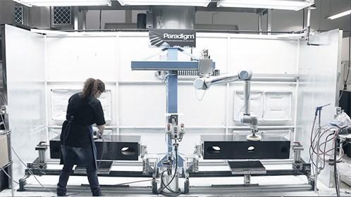 UR10机器人与员工并肩工作,为扬声器箱进行打磨抛光