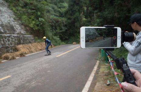 一名摄影爱好者用稳定器拍摄滑板画面