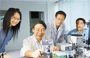 牛憨笨院士(左二)在指导青年老师和研究生。(深圳大学资料图片)
